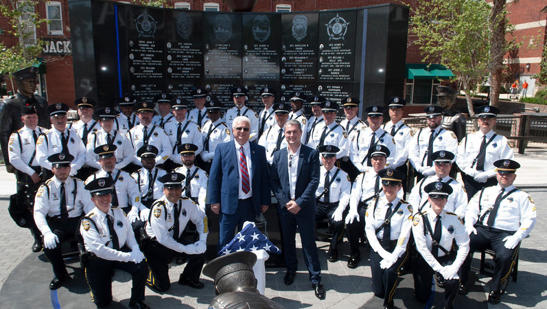 Lazar Finker and Eugene Frenkel stand with police officers in front of a police memorial wall in Jacksonville, Florida.